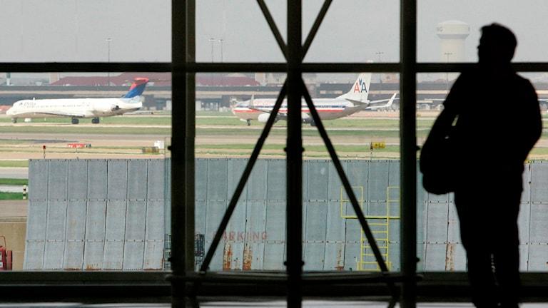 Väntsal på en flygplats, siluett av en person mot fönster.