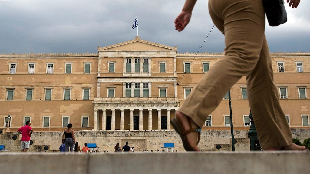 Människor går förbi det grekiska parlamentet i Aten. Foto: Petros Giannakouris/TT.