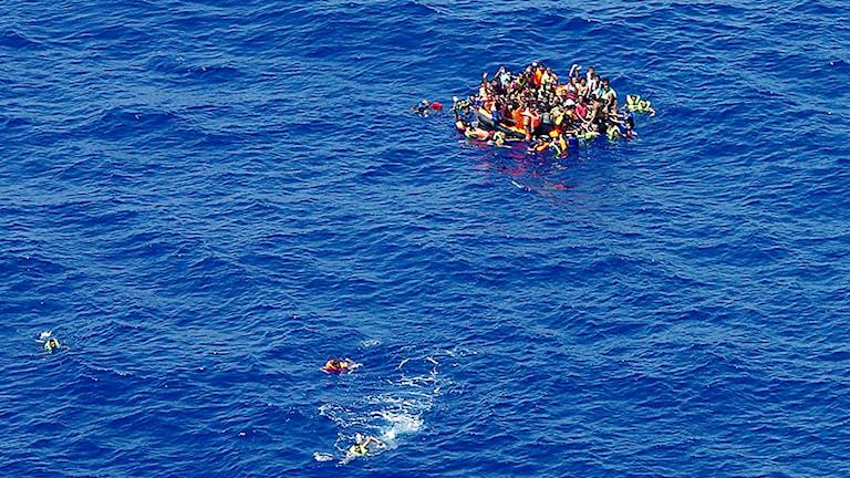 Några migranter simmar medan några andra tagit sig upp på en båt i väntan på att bli räddade utanför Libyens kust. Foto: Italienska kustbevakningen/TT.