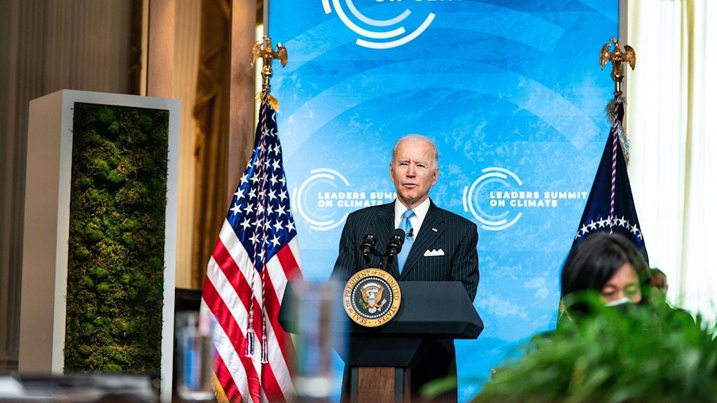 President Joe Biden vid ett podie med en amerikansk flagga till höger och en blå skylt bakom.