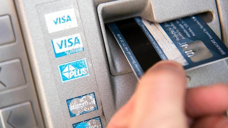 En person tar ut pengar i en bankomat med ett bankkort.