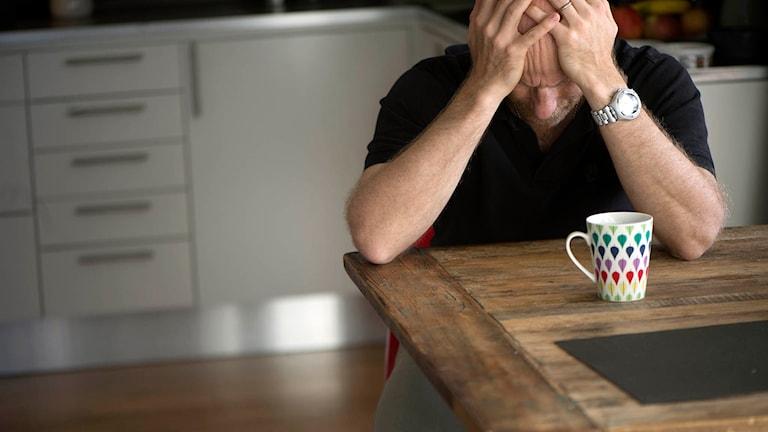 n deprimerad man sitter ensam hemma vid köksbordet med huvudet i händerna. Foto: Fredrik Sandberg / TT.
