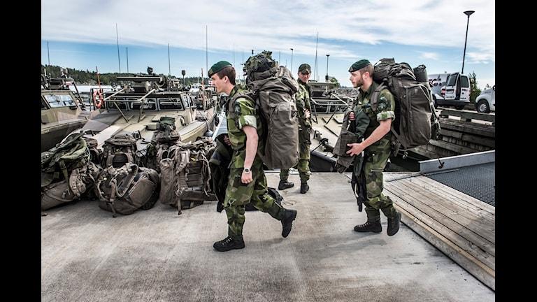 Två soldater går med tunga ryggsäckar. Foto: Lars Pehrson/TT.