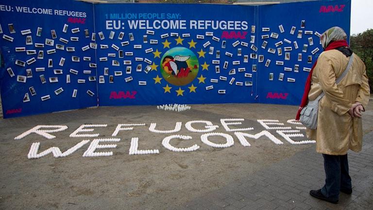 En tavla utanför EU-högkvarteret i Bryssel visar bild på den döde flyktingpojken Alan Kurdi. Foto: Virginia Mayo/TT.