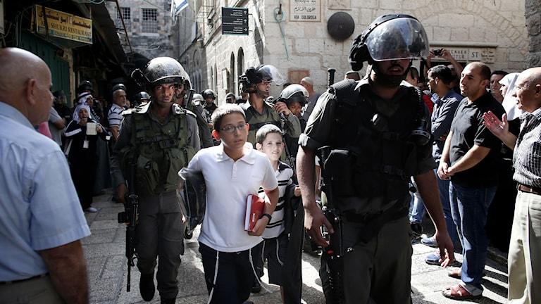 Israeliska säkerhetsstyrkor eskorterar judar som kommit för att be vid den västra muren. Foto: Thomas Coex/AFP