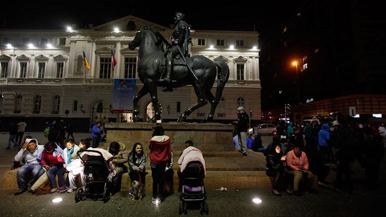 Människor sitter vid foten av en staty av en man till häst.