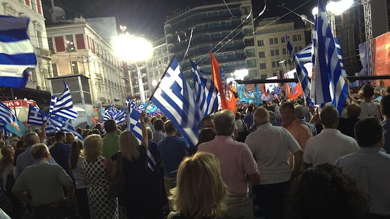 Grekiska flaggor vajar över en folkmassa på ett valmöte.