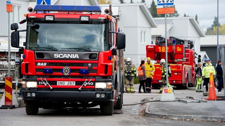 Räddningstjänstens brandbilar, en släckbil och en stegbil (i bakgrunden) samt brandmän Foto: Pontus Lundahl / SCANPIX