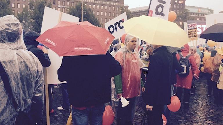 Demonstrerar i regnet mot nedskärningar. Nära 30 000 var på plats i Helsingfors. Foto: Thella Johnson7Sveriges Radio.