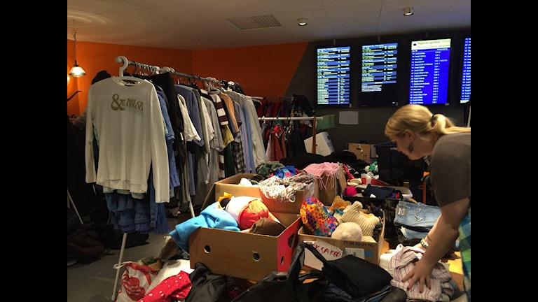 Bilden visar en klädstång och skänkta kläder i en tillfällig lokal på Malmö centralstation. Kläderna är för nyanlända asylsökande. Lokalen sköts av frivilliga. På väggen syns bildskärmar med tågens ankomsttider. Foto: Anna Bubenko/Sveriges Radio.