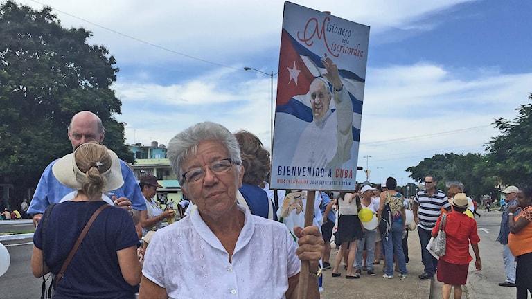 Kubanskan Maria Mesa håller upp ett plakat med påvens bild på. Foto: Lotten Collin/Sveriges Radio.