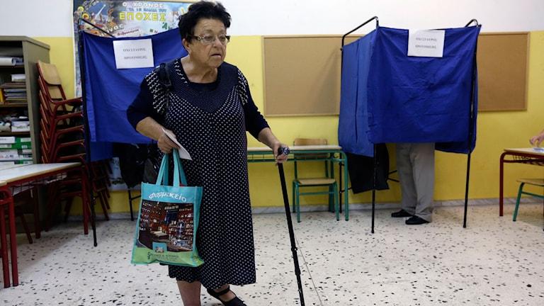 Grekisk kvinna går för att rösta. Foto:Thanassis Stavrakis/AP