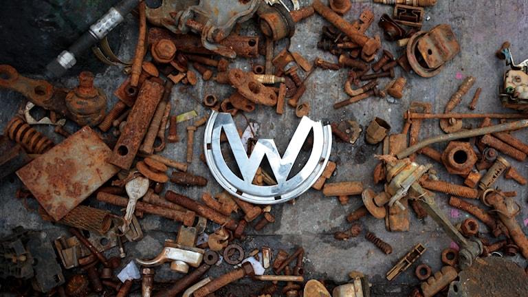 En Volkswagen-logga ligger bland rostiga bildelar. Foto: AP Photo/Sofia Jaramillo/TT.