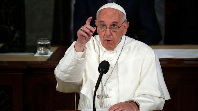 Påven håller tal, räcker upp fingret, klädd i vitt.