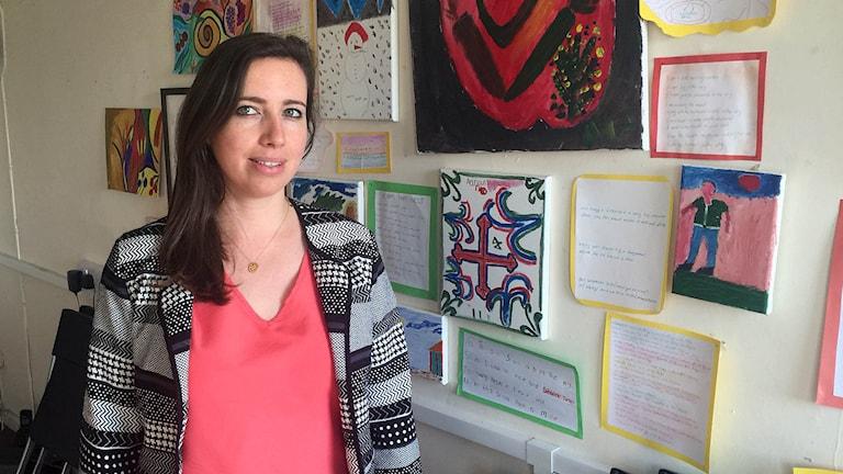 Jessica Maddocks framför teckningar som flyktingbarnen gjort. Foto: Staffan Sonning/Sveriges Radio.