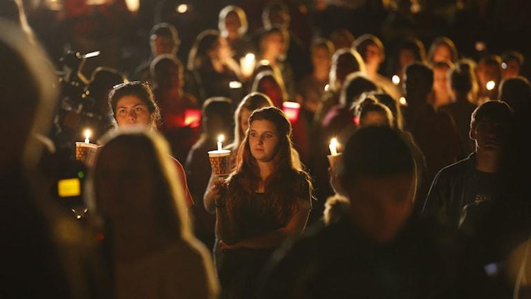 Människor samlas i Roseburg och tänder ljus för skolskjutningens offer. Foto: Randy L. Rasmussen/TT.