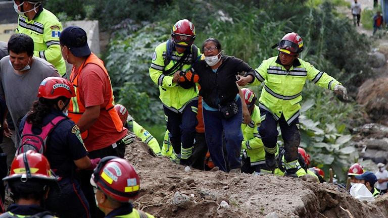 Räddningsarbetare hjälper en kvinna som just identifierat två omkomna familjemedlemmar. Foto: Luis Soto/TT.