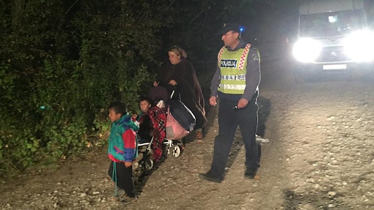 Barnfamilj på flykt i natten polis bil med tända lyktor i bakgrunden