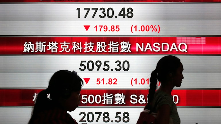 Två kvinnor går förbi en skylt från Hongkongbörsen.