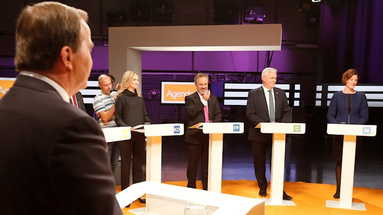 Löfvens nacke närmast i bild med fyra andra partiledare vända mot honom