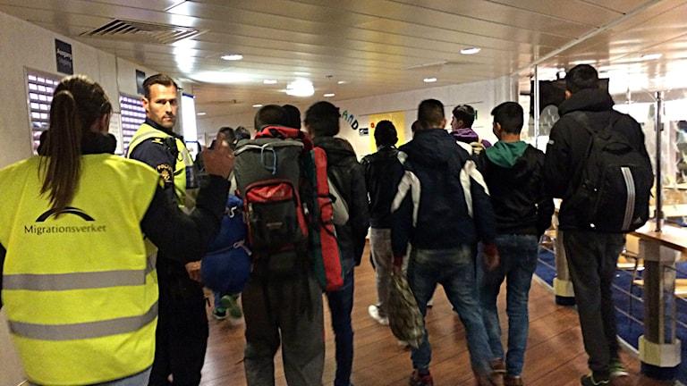 Bilden visar ryggen på en tjänsteman från Migrationsverket och en polis och ett antal flyktingar (bakifrån) ombord på en av färjorna från Rostock till Trelleborg. Foto: Anna Bubenko/Sveriges Radio.