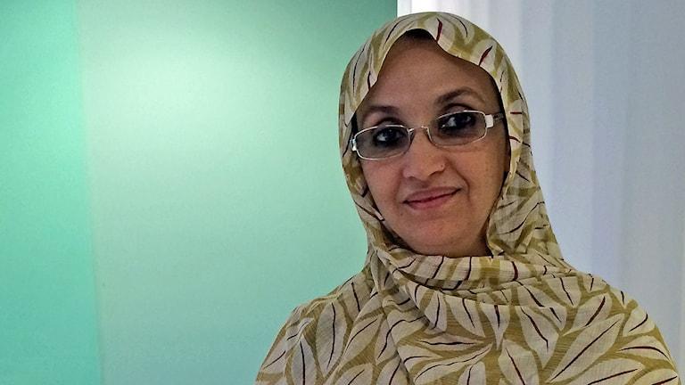 Kvinna med glasögon och bladmönstrad sjal. Ljusgrön och vit bakgrund.