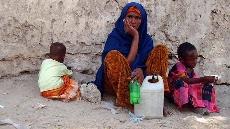 Somalisk kvinna med två barn sitter vid en husvägg.