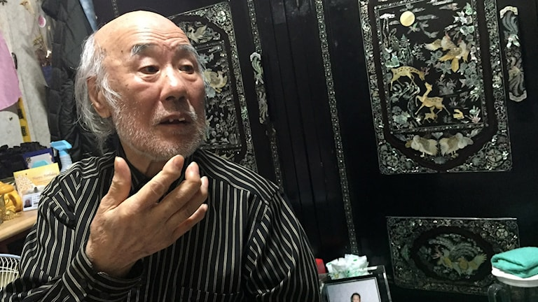 Koreansk man framför ett svart lackskåp med fågelfenixintartia.