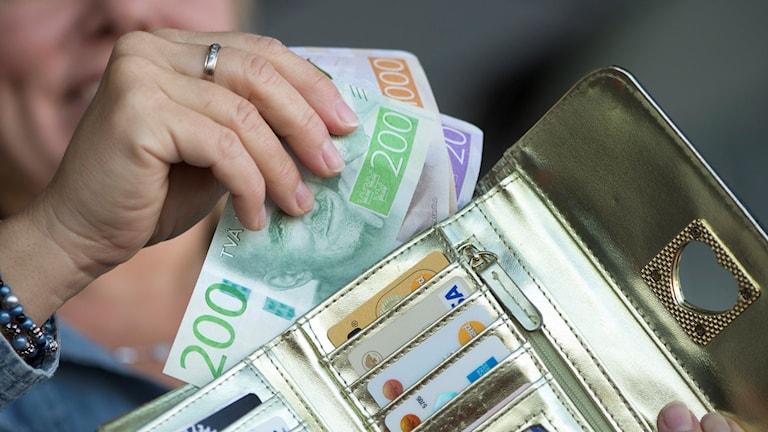 Kvinna håller upp svenska sedlar. Foto: Fredrik Sandberg/TT.