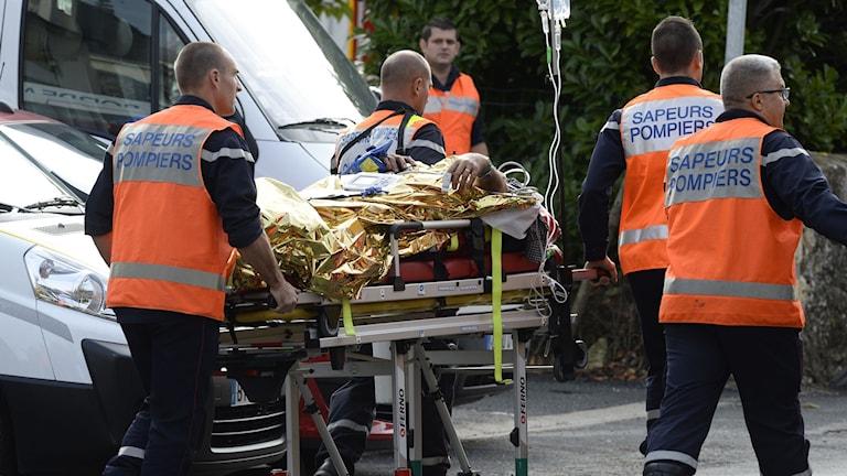 Räddningstjänst för bort en skadad person efter den svåra trafikolyckan i sydvästra Frankrike. Foto: Jean-Pierre Muller/TT.