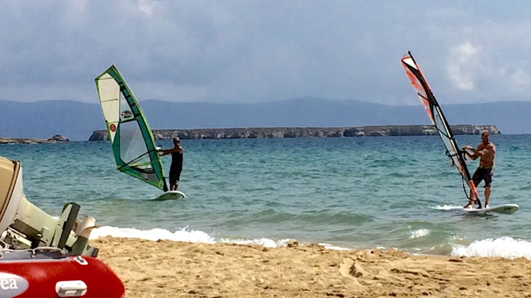 Två vindsurfare surfar på havet nära en sandstrand på den grekiska ön Paros. Foto: Maria Eksedler/Sveriges Radio.