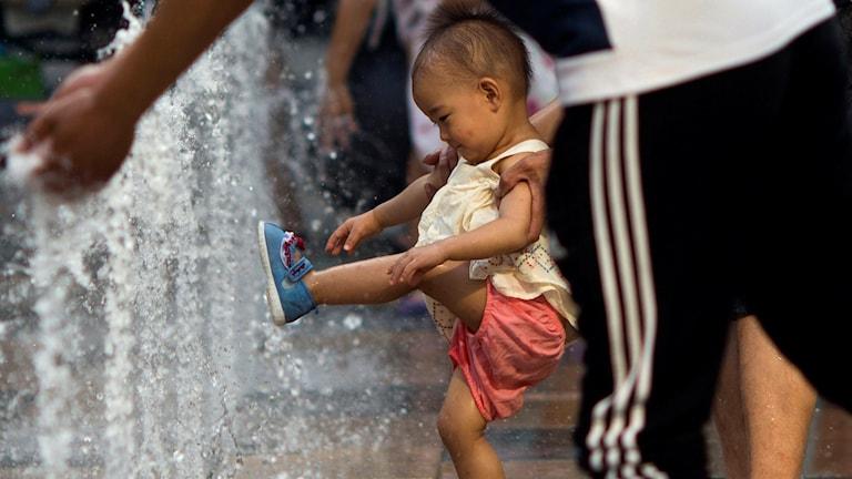 Kinesiskt barn leker i vatten. Foto: Ng Han Guan/TT.