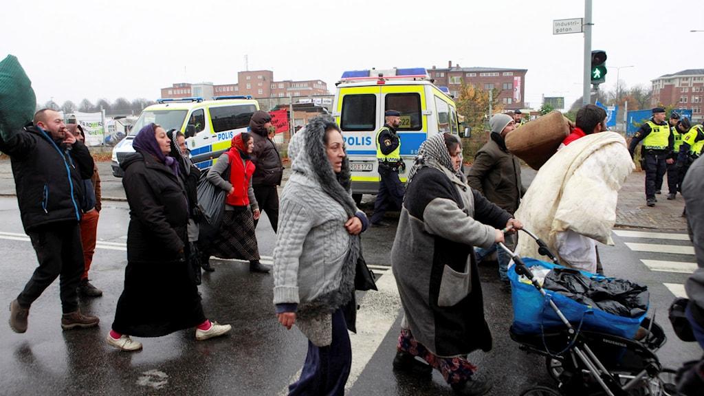 EU-migranter lämnar lägret på Industrigatan i Malmö. Tidigt på tisdagsmorgonen inledde polisen en insats för att tömma lägret. Foto: Drago Prvulovic/TT.