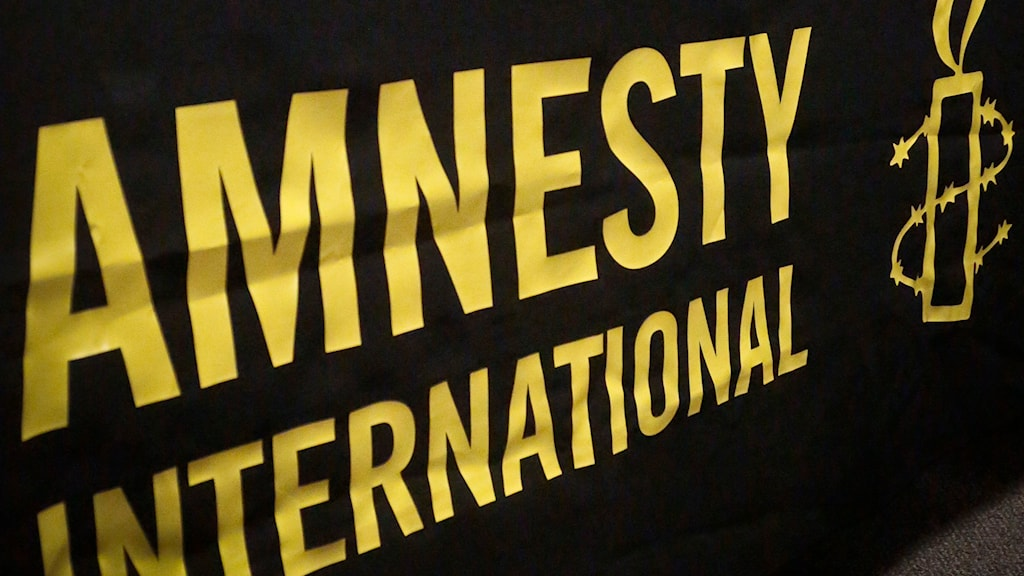 Logga skriven med gul text på svart tyg.