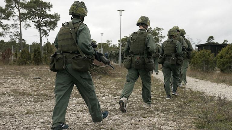 Militärer i gröna uniformer marscherar i led. Foto: Johannes Ledel/Sveriges Radio.