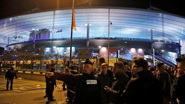 En polis står utanför Stade de France och dirigerar om folk. Foto: Michel Euler/TT.