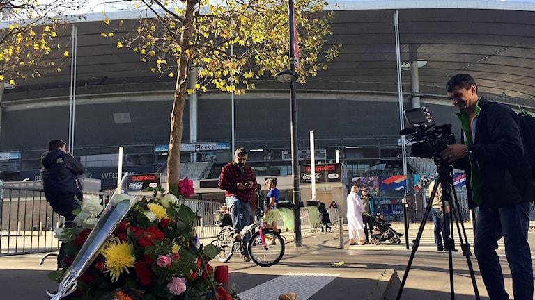Blommor och ljus har tänts utanför fotbollsarenan Stade de France. Foto: Beatrice Janzon/Sveriges Radio.