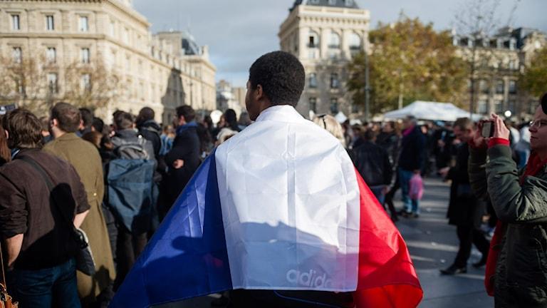 Tyst minut i Paris, bild på man bakifrån med fransk flagga insvept runtom sig