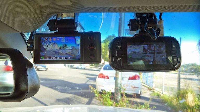 Två kameror som filmar fram genom vindrutan på en bil.