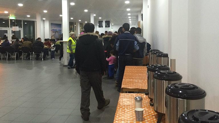 Bilden visar flyktingar i matkö i Malmömässans lokaler som tillfälligt hyrts som väntrum av Migrationsverket. Foto: Anna Bubenko/Sveriges Radio.