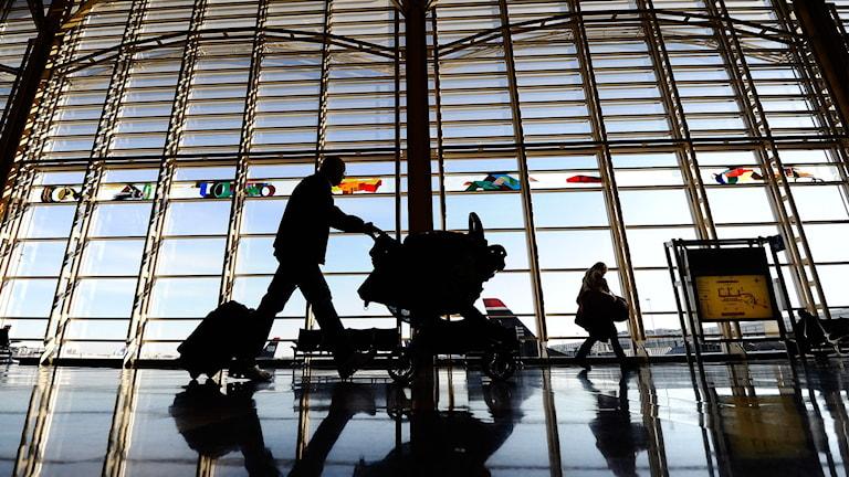 Bilden illustrerar passagerare med bagage på flygplats.