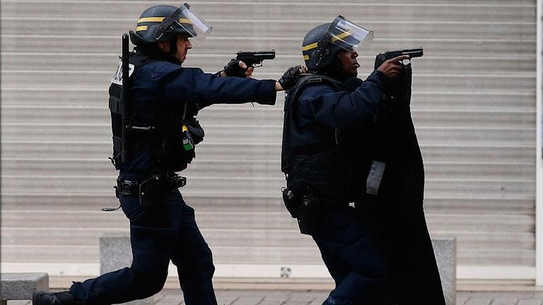 Två poliser under operationen i Saint Denis
