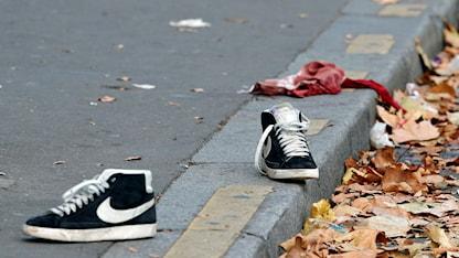 Skor och blodig tygbit på trotoaren. Foto: Christophe Ena/TT.