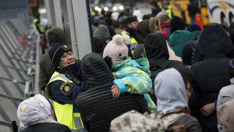 Bilden visar ett antal flyktingar som just kommit till Hyllie station i Malmö. En polis försöker muntra upp en liten flicka. Foto: Johan Nilsson/TT.
