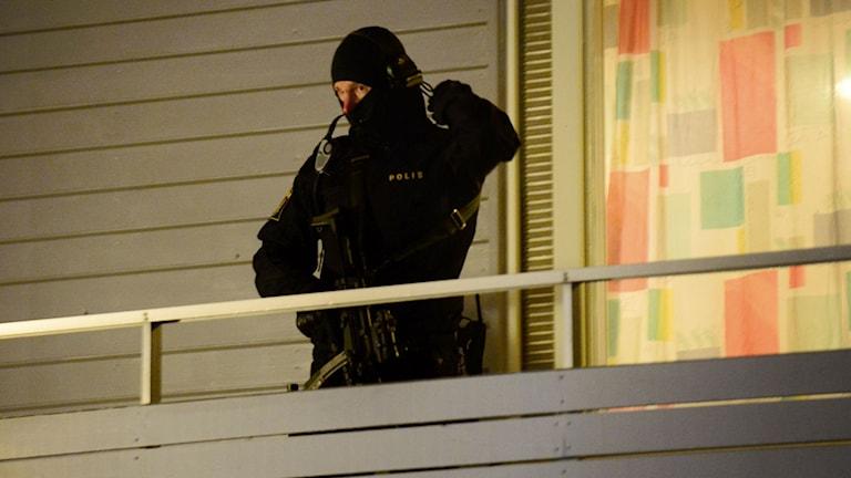 Tungt beväpnad polis på loftgången till radhus i Boliden. Foto: Robert Granström/TT.
