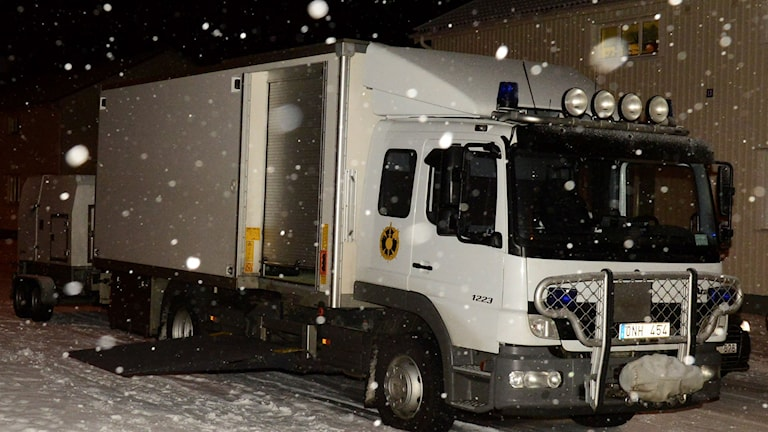 Snön faller runt polisens bombbil i Boliden. Foto: Robert Granström / TT.