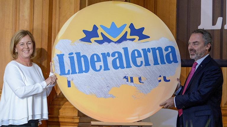 Partiledaren Jan Bjöklund (t h) gör ett symboliskt namnbyte till Liberalerna efter omröstningen på Folkpartiets landsmöte i riksdagshuset på söndagen. På sitt landsmöte i dag har Folkpartiet bytt namn till Liberalerna. Foto: Janerik Henriksson / TT