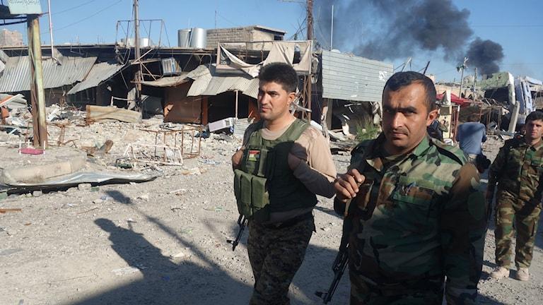 Peshmergastyrkor går längs en sönderbombad gata i Sinjar. Foto: Katja Magnusson/Sveriges Radio.