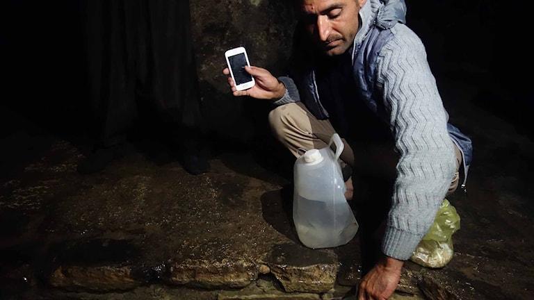 En yazidisk man som snart ska fly mot Europa hämtar heligt vatten och får välsignelser inför resan i Lalish. Foto: Katja Magnusson/Sveriges Radio