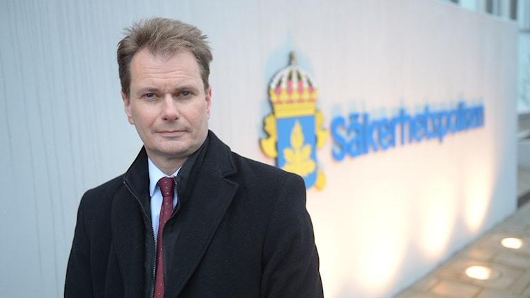 Säkerhetspolisens biträdande chef framför säkerhetspolisens logotyp. Foto: Maja Suslin/TT.